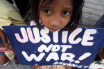 A Filipino child holds a placard during a rally against police brutalities